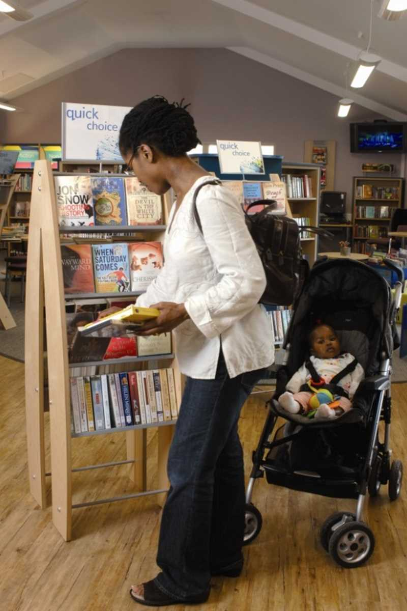 Parent and child in pushchair browsing library books
